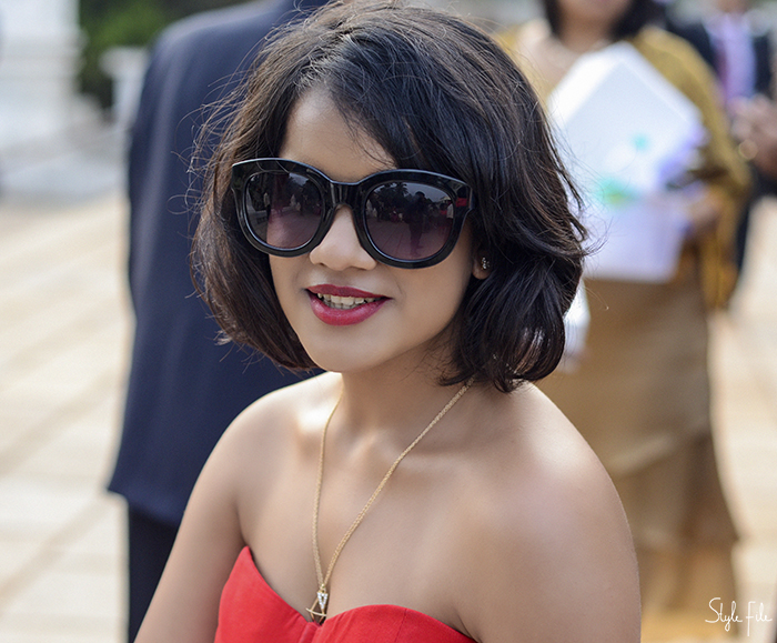 Woman smiles while wearing cat eye sunglasses with red lips, layered gold necklace and red strapless dress
