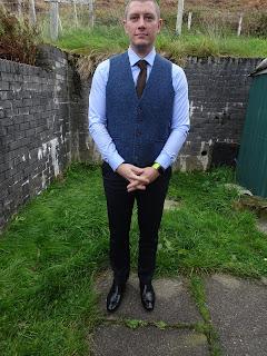 handsome man in tweed waist coat and light blue shirt