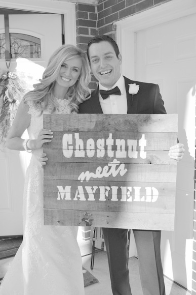 These happy newlyweds hold up a handmade pallet sign on their wedding day.