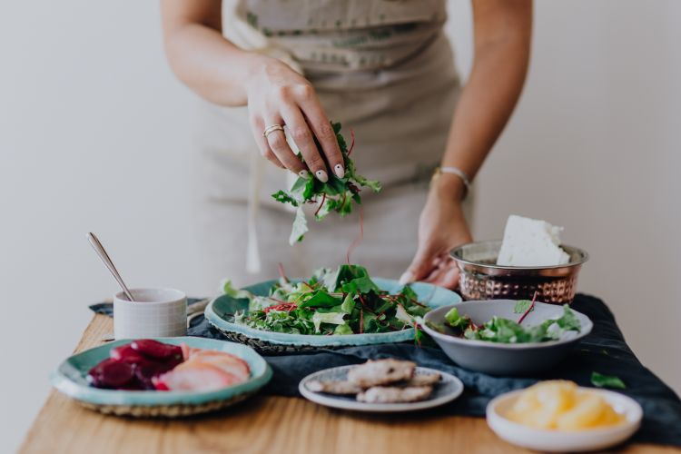 woman preparing a healthy lunch with salad leaves and plates of food
