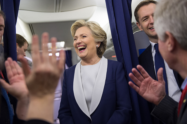 image of Hillary Clinton smiling broadly and laughing on her plane, surrounded by a bunch of people