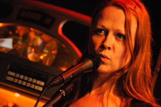 Photo of poet Jeanann Verlee speaking into a microphone. She has long, reddish hair. There is a jukebox in the background.