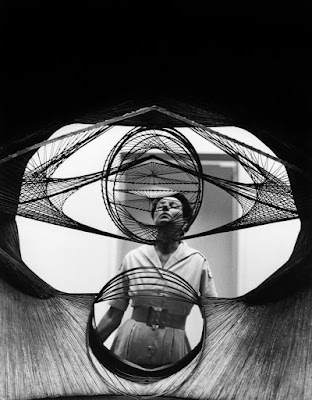 Roloff Beny fotografierte Peggy Guggenheim auf der Biennale in Venedig durch die Skulptur Developable Surface des Künstlers Antoine Pevsner hindurch. © Roloff Beny / Courtesy of National Archives of Canada