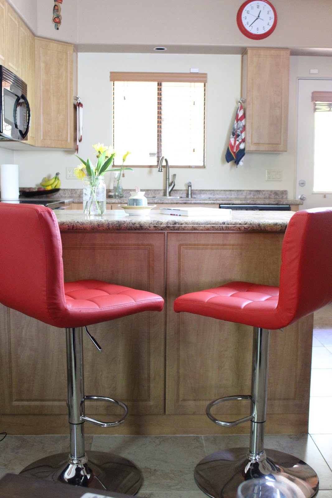 A bright view of the kitchen, featuring two red kitchen chairs and a unique butter crock and a coffee book.