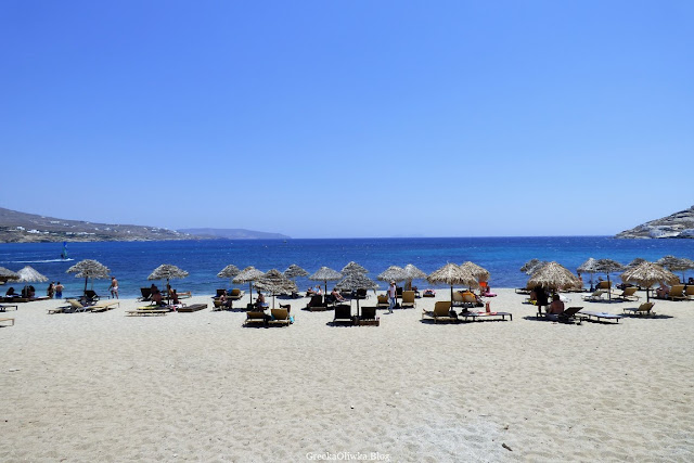 Parasole i leżaki na plaży Mykonos. Błękitne greckie niebo, lazurowe morze.