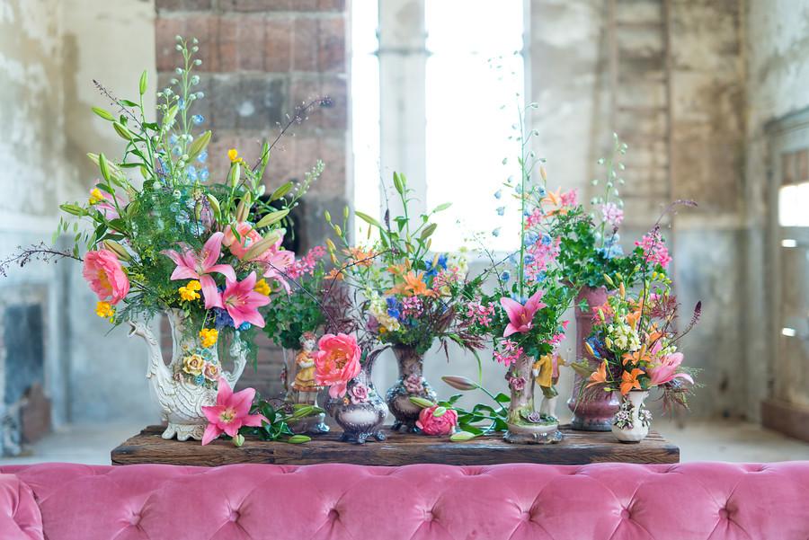 jarrones con dalias rosa chicle y otras flores en tonos verdes y pastel