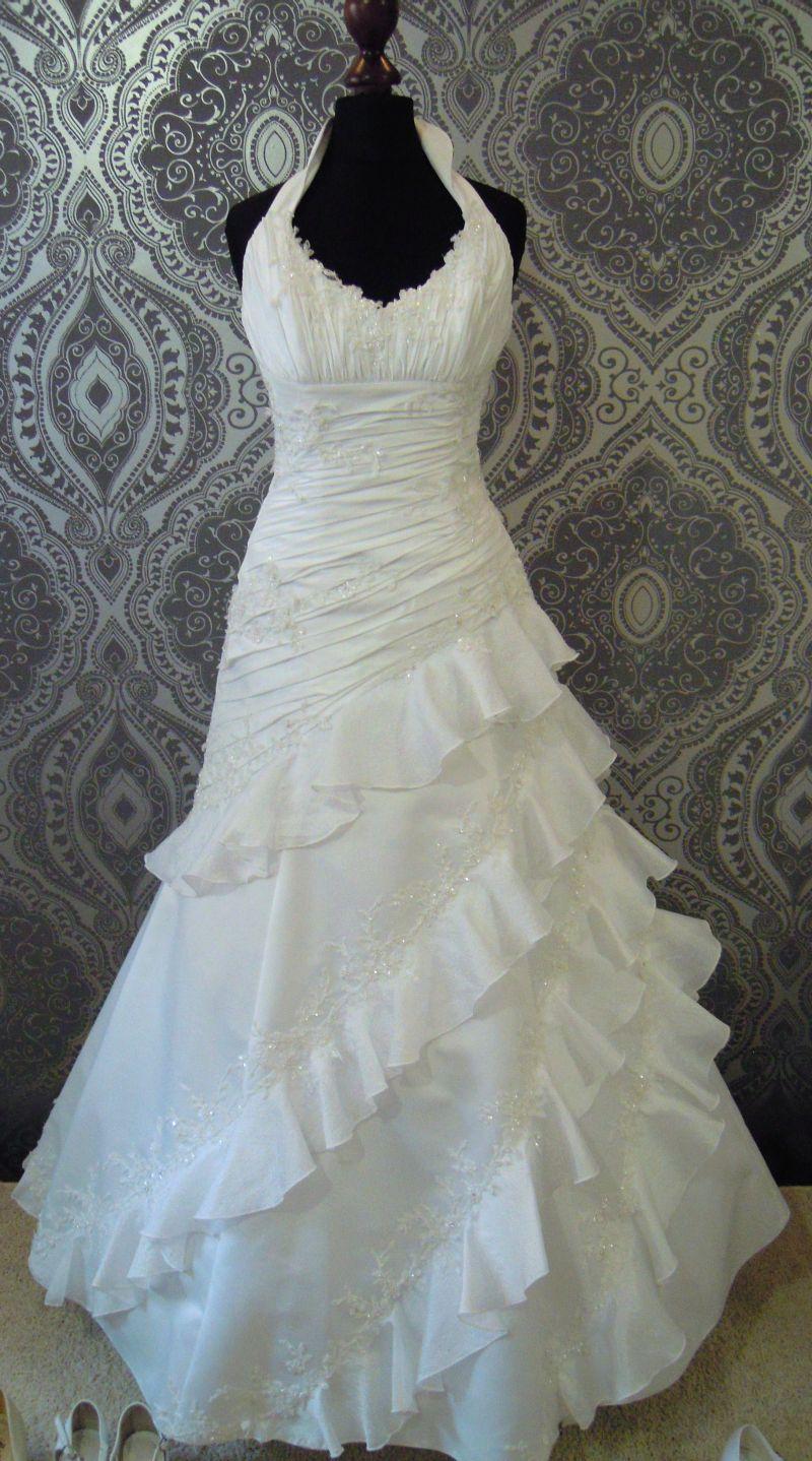 4944dc995a Suknia ślubna z falbankami. Wykonana z dwóch rodzajów materiałów. Ramiączka  zapinane na szyi. Ozdobiona koronką. Sukienka biała