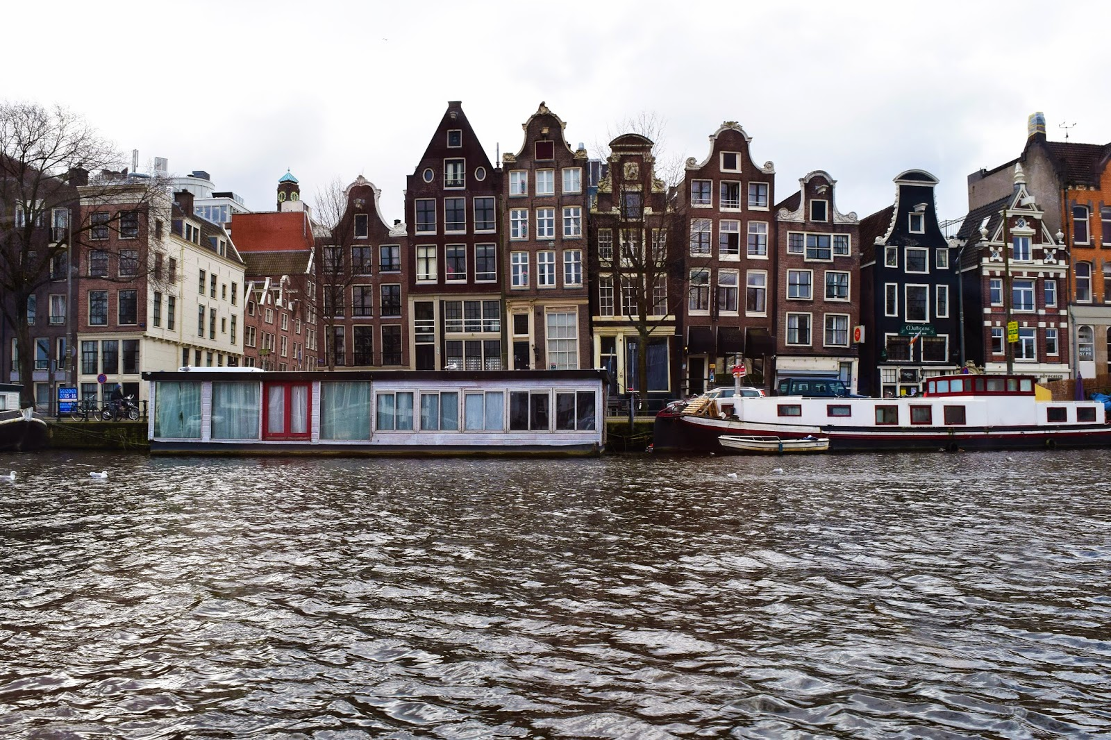 Taken from a canal boat looking across one of the wider canals in Amsterdam. In the background you can see two house boats and behind those the famous thin houses stacked side by side
