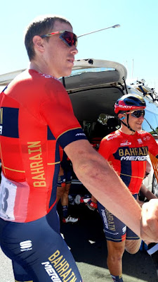 Rohan Dennis is on the left and Domenico Pozzovivo is on the right with the back of the team van open behind them. They are looking towards the right while chatting with fans (not in the picture). Their team guernseys are red with navy strips on the cuffs,front and back and the word 'Bahrain' in gold and 'Merida' in white. Domenico Pozzovivo is wearing a helmet and sunglasses. Rohan Dennis is not wearing a helmet, only sunglasses.  Rohan Dennis has a light stripe (tan line) on the side of his face running from his ear to his chin where his helmet straps usually sit.