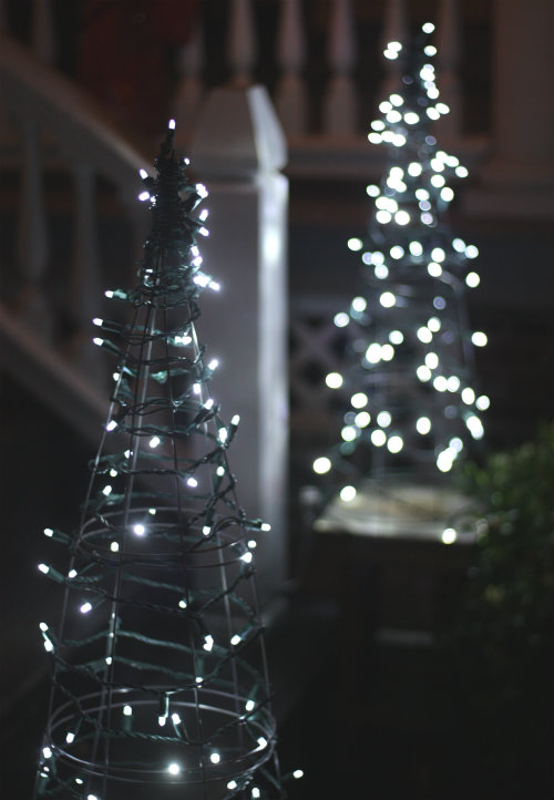 over the weekend we tackled a fun and easy little christmas decor operation making lit up christmas tree decorations from tomato cages and a string of led