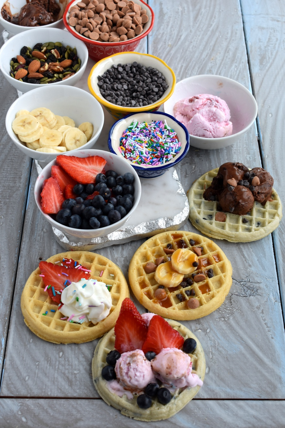 Dessert Waffle Bar is super easy to make and has tons of fun toppings like whipped cream, chocolate chips, caramel, bananas, strawberries, blueberries, chocolate sauce, nuts, sprinkles and different kinds of ice cream.
