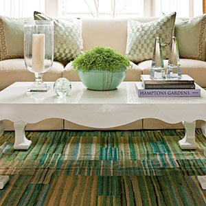 This modern coffee table compliments the glass vase and candle decor piece.