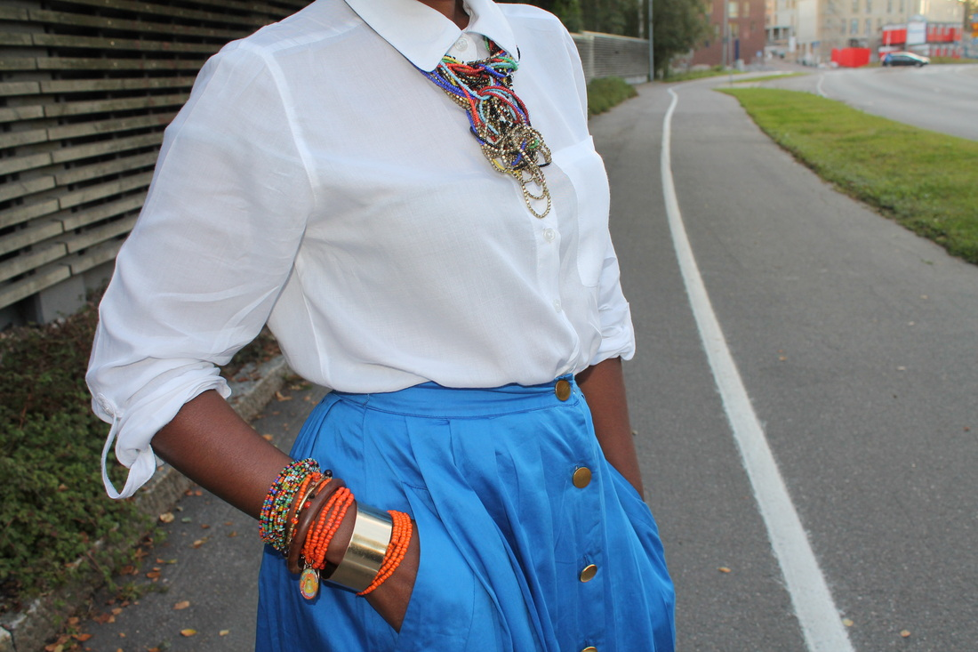 dark skinned woman wearing white shirt, blue skirt, and colorful neck piece