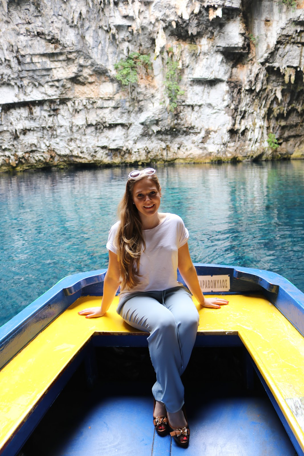 Blonde girl wearing white t shirt and blue trousers in a boat in Melissani Cave, Kefalonia