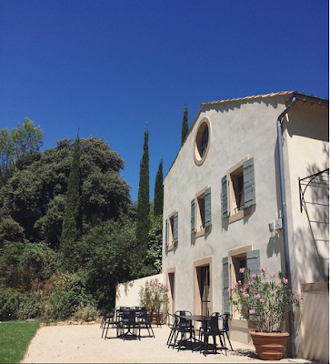 Luberon Region garden with gravel and black iron chairs