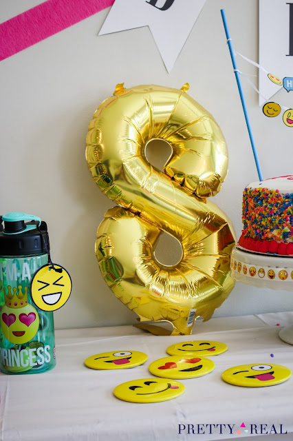 foil balloon and emoji pins for an emoji birthday party