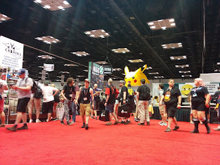 A view of the exhibit hall at Gen Con, with people walking amongst the booths, which have a variety of signs both on the booth itself and hanging from the ceiling, including a giant inflatable Pikachu visible in the background.