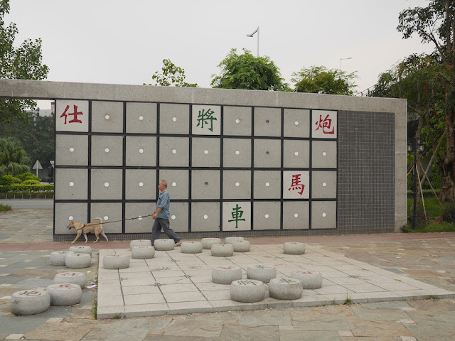 man walking a dog by a xiangqi sculpture at the Dragon Boat Cultural Park (龙舟文化公园) in Zhongshan