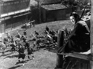 Toshiro Mifune as Sanjuro in Akira Kurosawa's Yojimbo, watches from a bell tower as the two opposing groups fight