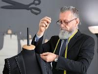 Bir ceketin yakasını diken ve boynunda bir mezura olan yaşlı ve sakallı bir terzi