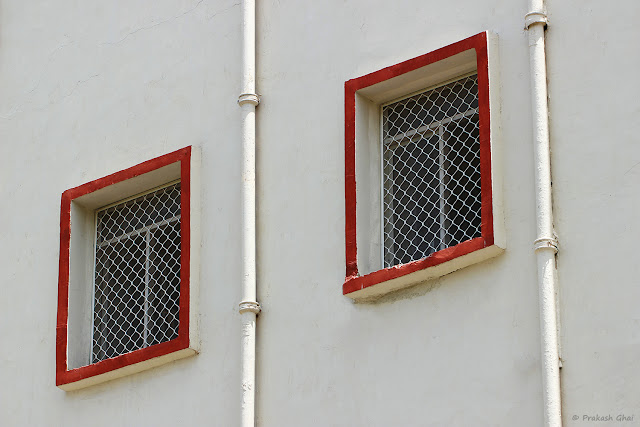 A Minimal Art Photograph of Two Windows with Red Borders on a White Wall shot by Canon 100 mm prime Macro lens on a Crop Sensor Canon 600D Camera. Picture taken at Ravindra Manch, Jaipur, (Rajasthan)  during Jaipur Art Summit.