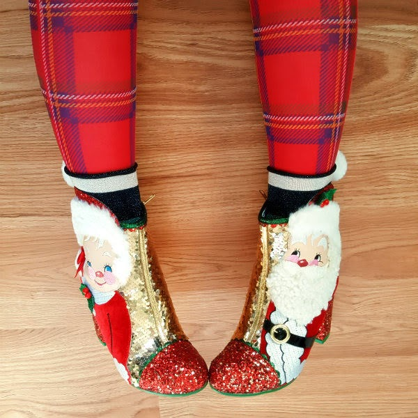legs on floor wearing tartan tights and Mr & Mrs Claus ankle boots