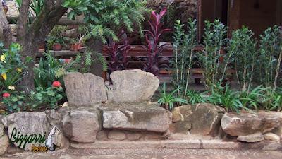 Detalhe do banco de pedra no jardim com pedras tipo chapas de pedra moledo com as muretas de pedra com o canteiro de agapanto, dracena vermelha com as mudas de murta.