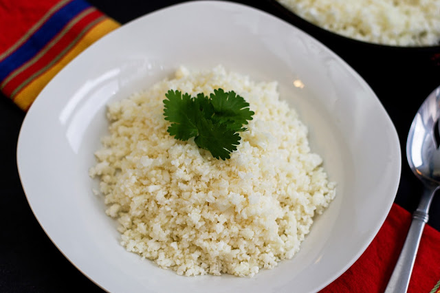 A white bowl of the finished, homemade, cauliflower rice with cilantro on top.