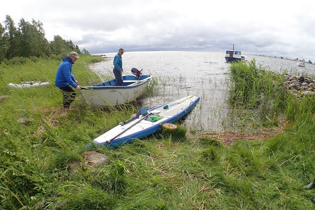 SUP-lauta, kaksi venettä ja kaksi ihmistä rannassa.