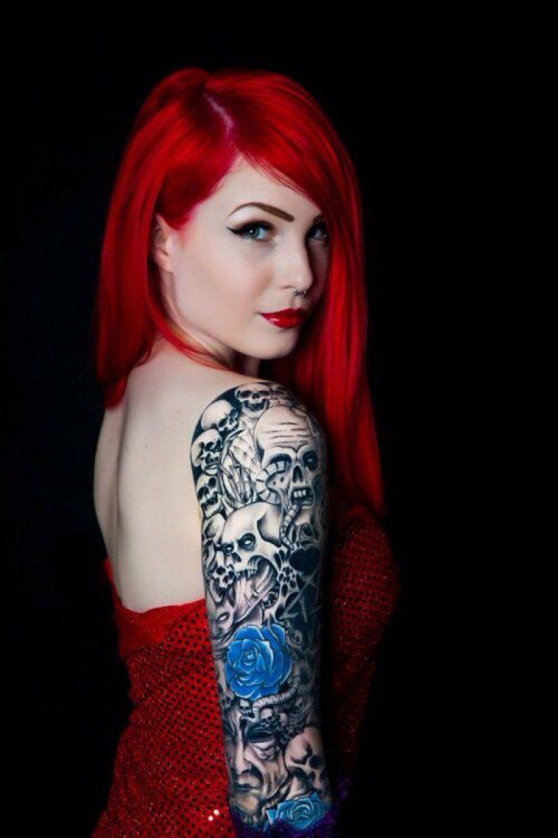 chica peliroja con tatuajes de calaveras y flores en el brazo