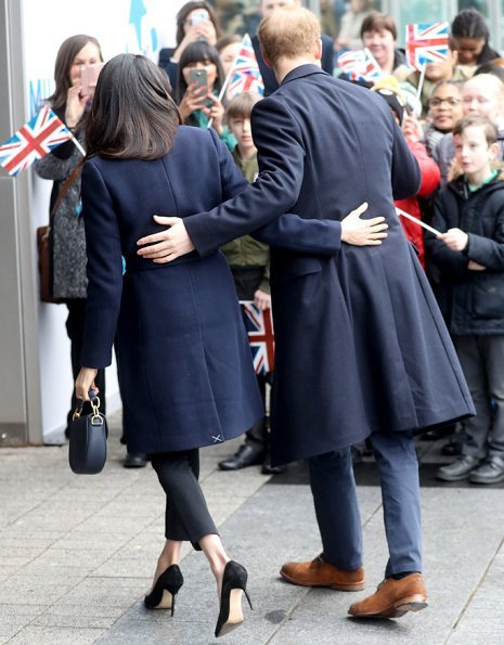 Meghan Markle wore J.Crew coat, Manolo Blahnik pumps, All Saints Ridley jumper, Alexander Wang Pants and carried Altuzarra Ghianda shoulder bag