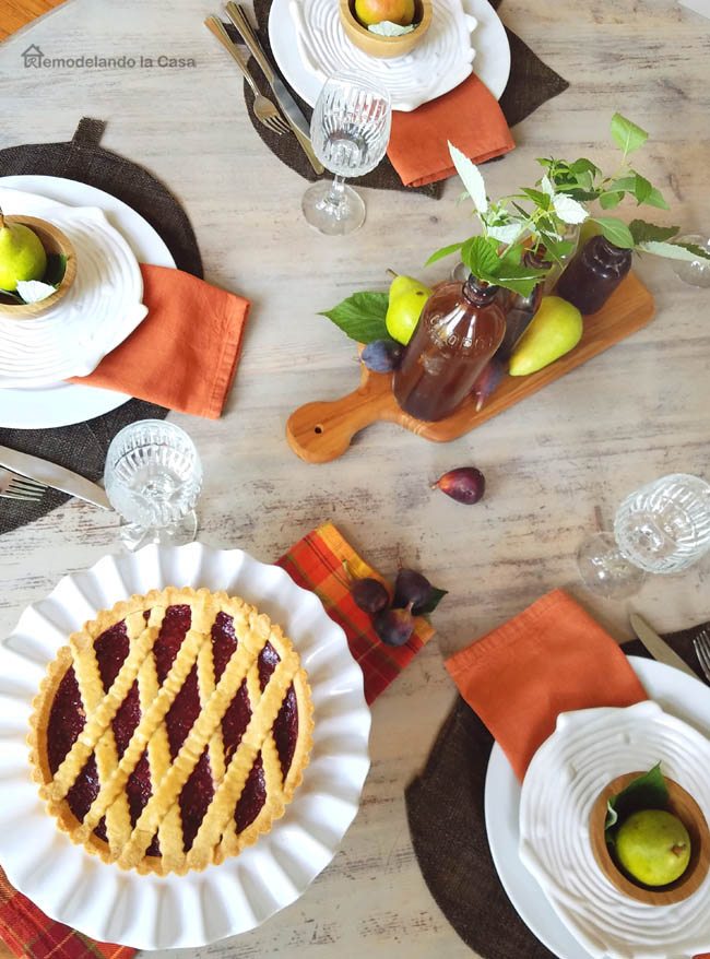 raspberry tarte on white ruffled stand, orange napkins, brown bottle centerpiece, log salad plates, pears in wooden bowls, figs, leaf placemats,