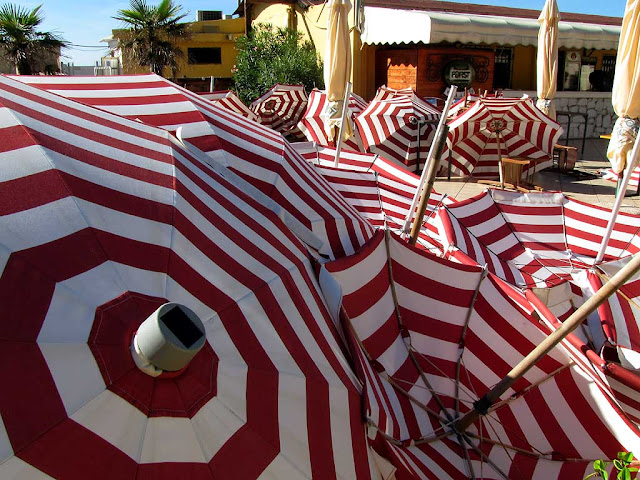 Checking parasols before storage, sea resort, Livorno