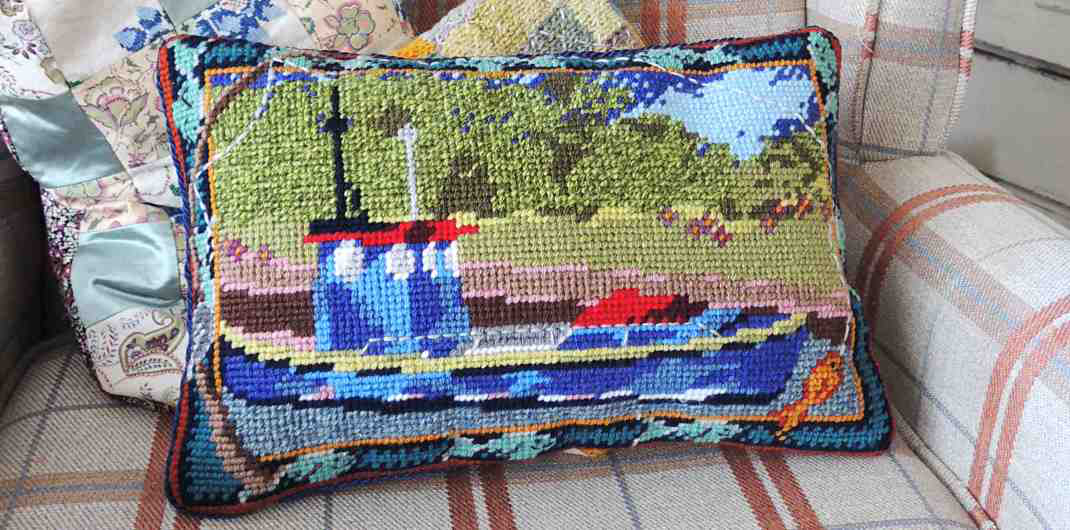 Tapestry needlepoint pillow with a river fishing boat design