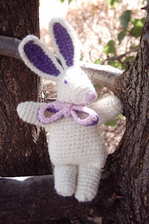 """Richard Rabbit"" crocheted toy sitting in the fork of a tree. The toy is white with purple inner ears, dark purple eyes and a mauve/purple crocheted bow around its neck."