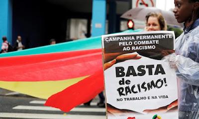 """Um demonstrador mantém uma bandeira que lê """"Basta do Racismo"""" durante o Dia Nacional da Consciência Negra em São Paulo, Brasil, no mês passado."""