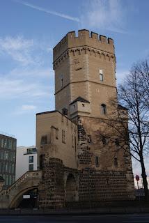 Brauner Turm mit Zinnenkrant und Bogentreppe