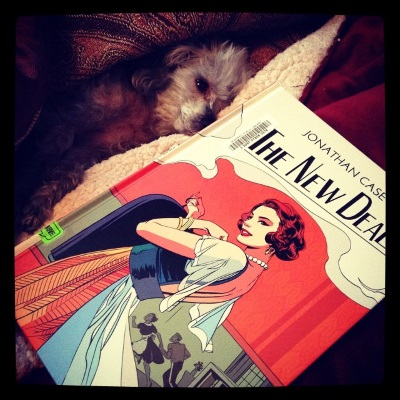 Murchie lays inside a blanket cave formed by a red tapestry comforter. A hardcover copy of The New Deal rests parallel to him. The cover features a red-haired white woman posing in 1930s evening wear against an orange background. In a grey-tinted panel behind her, a black maid and a white bellhop race madly along.