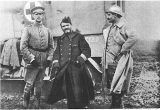 Black and white photo of three military commanders standing in front of a what appears to be a metal container with a cross sign on it. One on the very right is wearing a German military winter uniform and the one right beside in the center is wearing a French military trench coat. Another guy is standing on the very right side with a thick but light-colored winter coat with a hard hat.