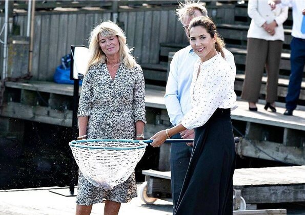 Crown Princess Mary wore a white printed shirt and black skirt. The thornback ray (Raja clavata) were released into Danish waters