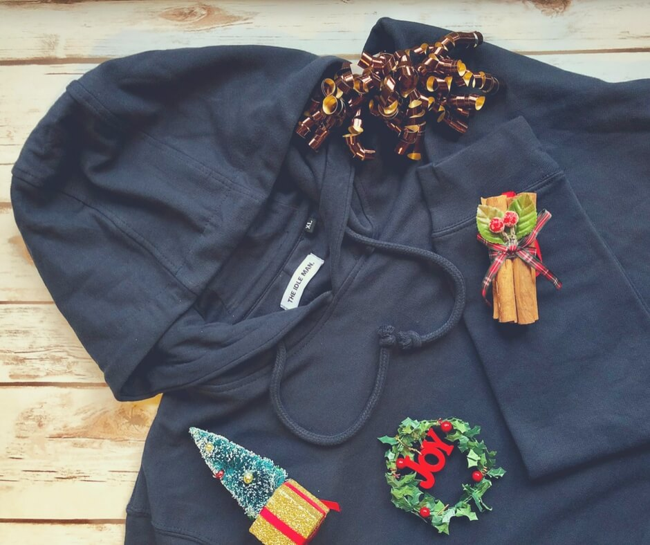 A navy hoodie with christmas decorations lying on it.
