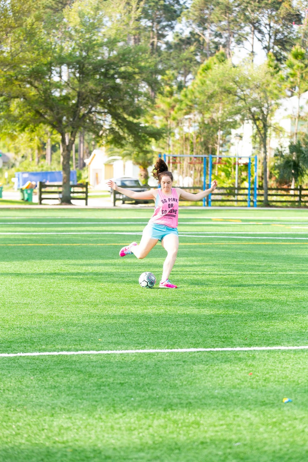 Brunette girl wearing victoria's secret pink tank top and nike blue running shorts playing soccer on a soccer field