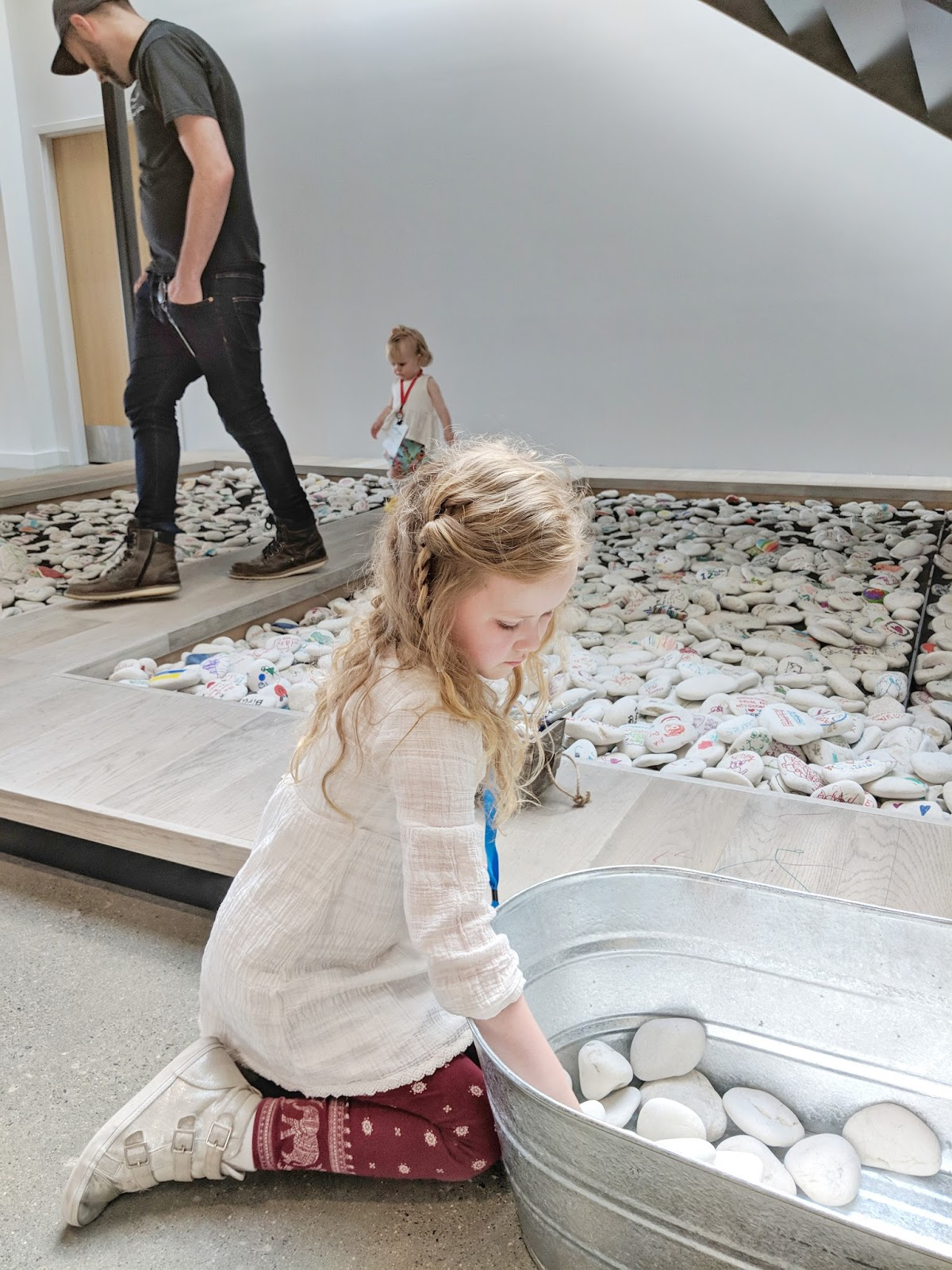 first grader choosing stone for rock garden concentrating