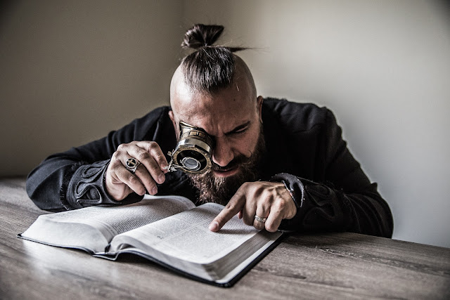 a man searching the bible with a magnifying glass