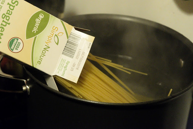 Spaghetti being added to a pot of salted, boiling water.