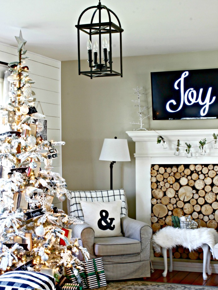 Smart tv with chalkboard look and flocked tree in Christmas room with plank wall and lantern light fixture chandelier - www.goldenboysandme.com