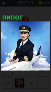Женщина пилот стоит в форме, облокотившись на модель самолета в облаках