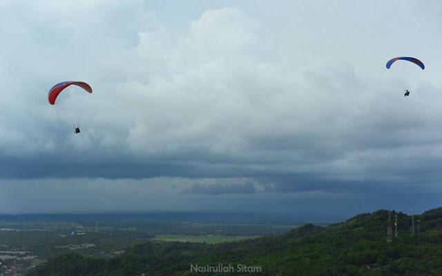 Paralayang terbang di atas para penunggu senja