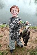 Photo of smiling boy holding freshly caught fish