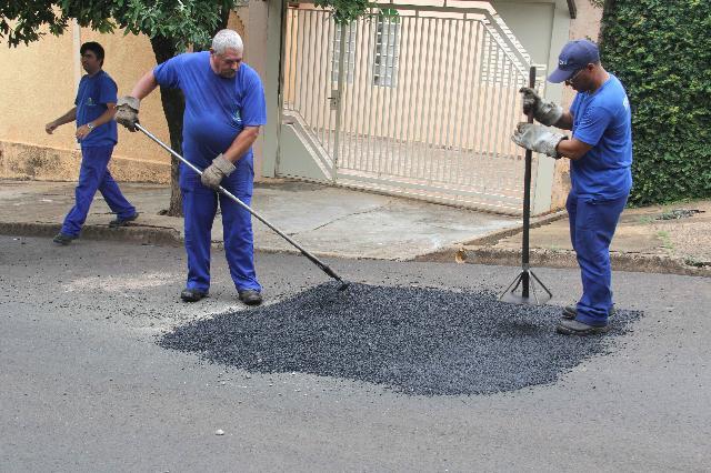 Dois funcionários da secretaria de Obras de Bauru fazendo o recapeamento de um buraco na frente de uma casa com portão branco